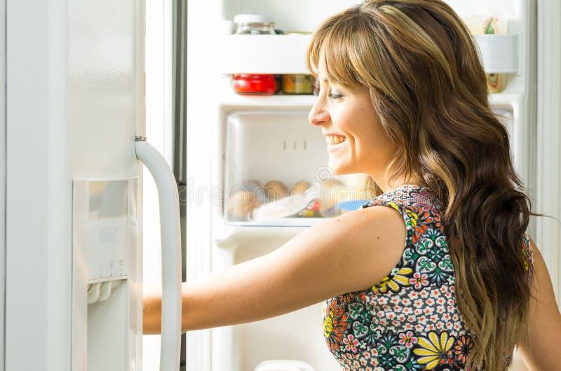 Kobieta jest ubranym kolorową suknię w nowożytnej kuchni zdjęcia stock