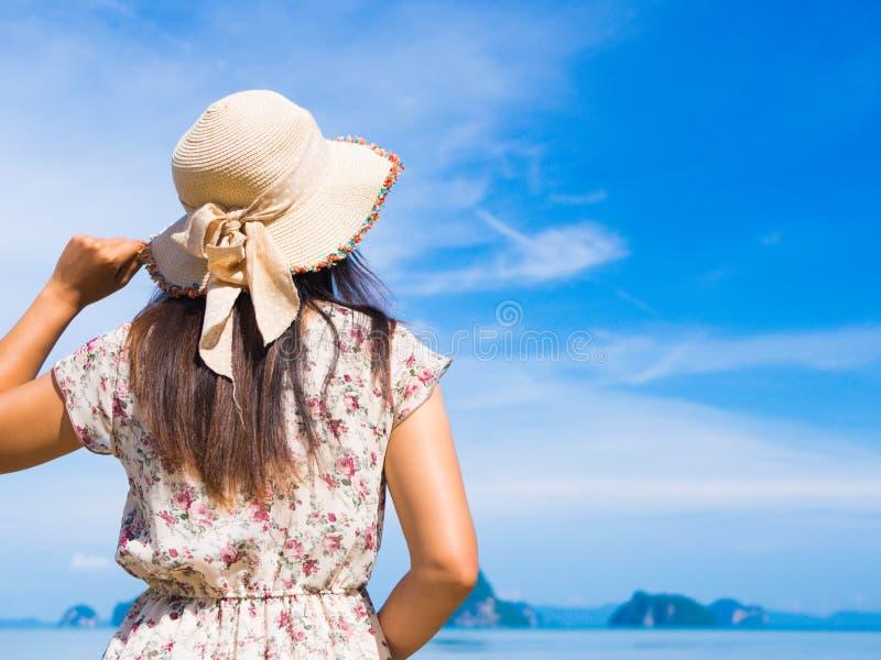 Kobieta jest ubranym słomianego kapeluszu i plaży suknię cieszy się widok przy oceanem w wakacje fotografia stock