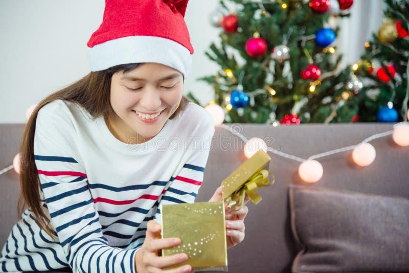 Kobieta jest ubranym Santa Claus kapelusz i otwiera Bożenarodzeniowego prezenta pudełko zdjęcie royalty free