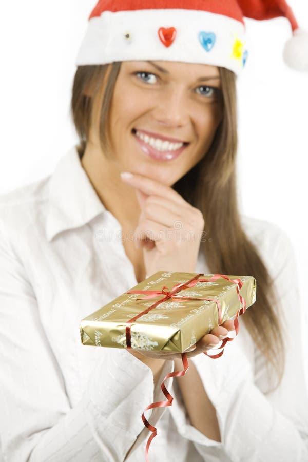 Kobieta jest ubranym Santa kapelusz trzyma prezent zdjęcia royalty free