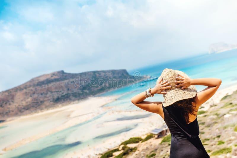 Kobieta jest ubranym strój jednoczęściowy i pływackiego kapelusz patrzeje morze od falez kostiumu i słomianego Kobieta cieszy się zdjęcie royalty free