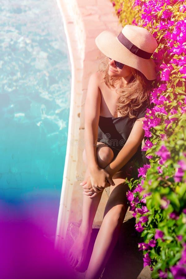 kobieta jest ubranym swimsuit przy basenem, ono uśmiecha się i dostaje garbnikujący, fotografia stock