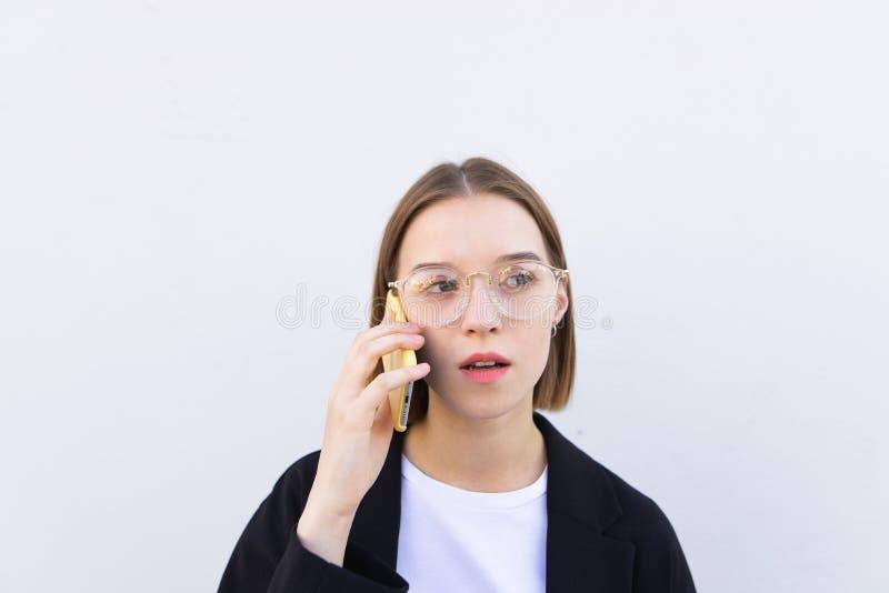 Kobieta jest ubranym szkła i czarna kurtka opowiada na smartphone na białym tle i patrzeje daleko od obrazy stock