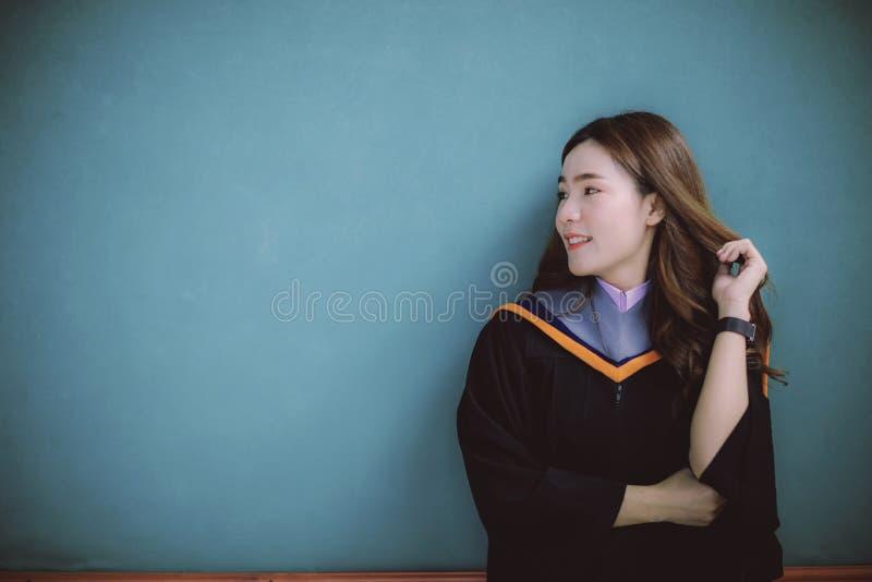 Kobieta jest ubranym uniwersytecką skalowanie kostiumu pozycję przeciw jasnej błękit ściany toothy uśmiechniętej twarzy z  obraz stock