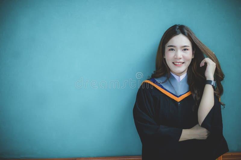 Kobieta jest ubranym uniwersytecką skalowanie kostiumu pozycję przeciw jasnej błękit ściany toothy uśmiechniętej twarzy z  zdjęcie royalty free