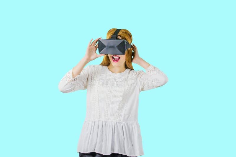 Kobieta jest ubranym vr słuchawki Młoda kobieta w białej bluzce z VR pióropuszem, szokujący spojrzenie panika nowy obraz stock