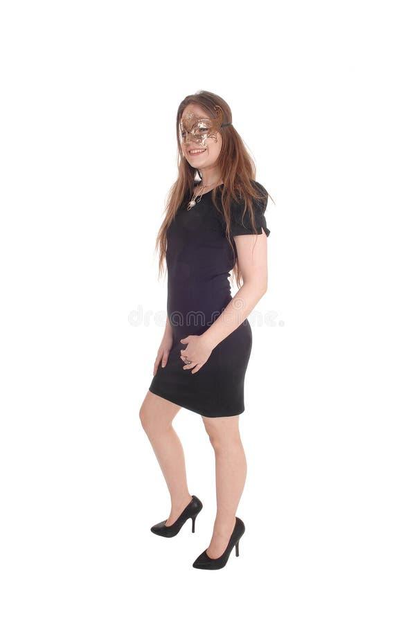 Kobieta jest ubranym złocistą maskę w czerni sukni zdjęcia royalty free