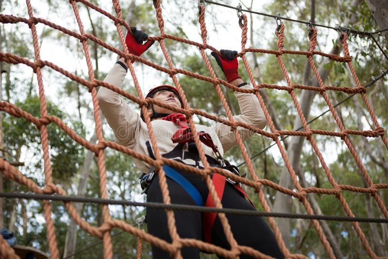 Kobieta jest ubranym zbawczego hełma pięcie na linowym ogrodzeniu fotografia royalty free