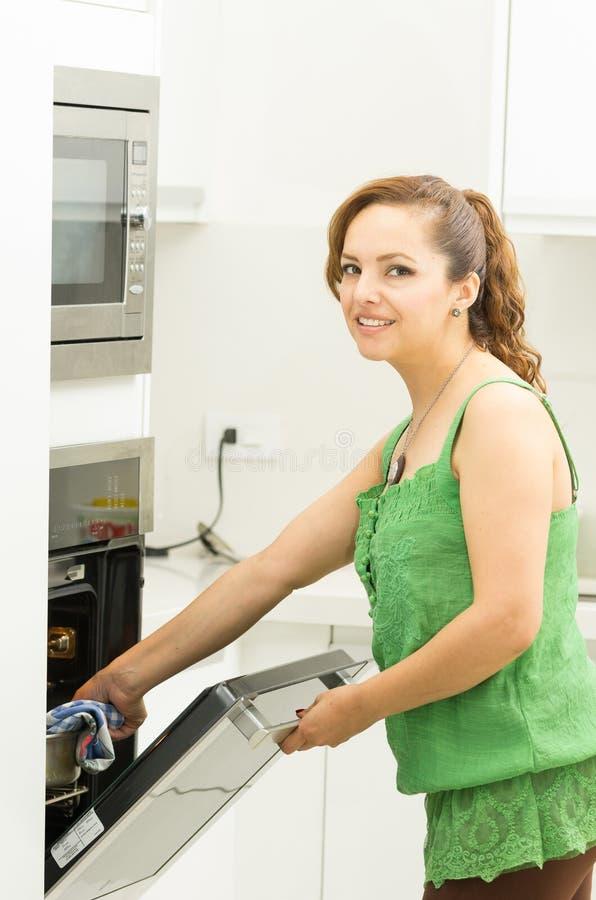 Kobieta jest ubranym zieleń wierzchołek w nowożytnym kuchennym mieniu obrazy royalty free