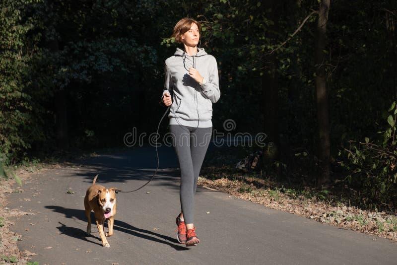 Kobieta jogging z psem w parku Młoda żeńska osoba z zwierzęcia domowego d zdjęcie royalty free