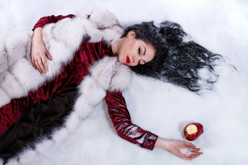 Kobieta kłaść na śniegu blisko gryźć jabłka zdjęcie stock