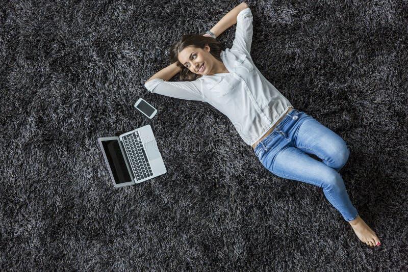 Kobieta kłaść na dywanie fotografia stock