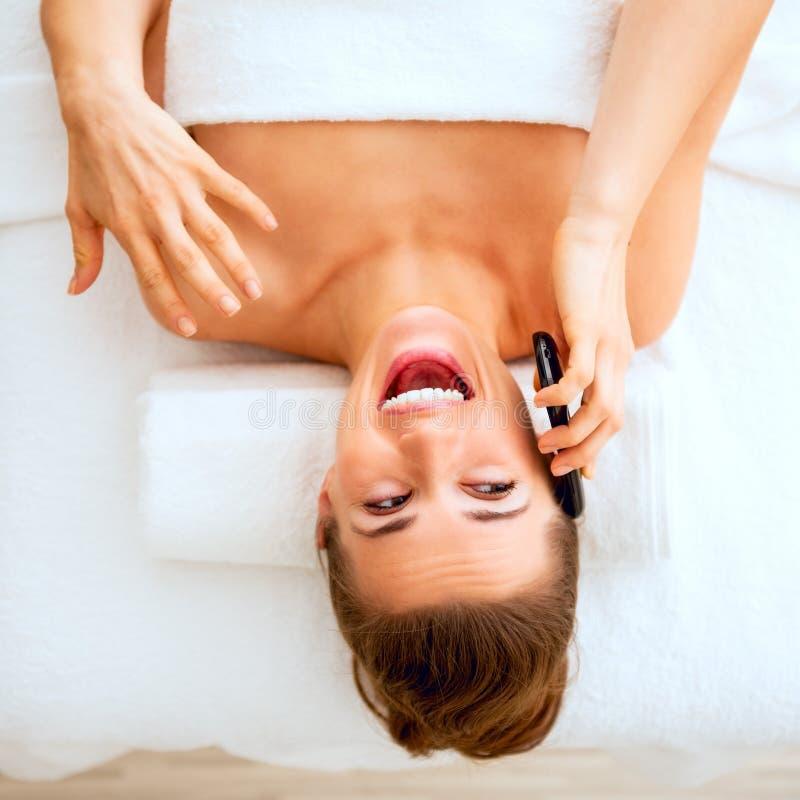 Kobieta kłaść na masażu stołowym i opowiada telefon komórkowego fotografia royalty free