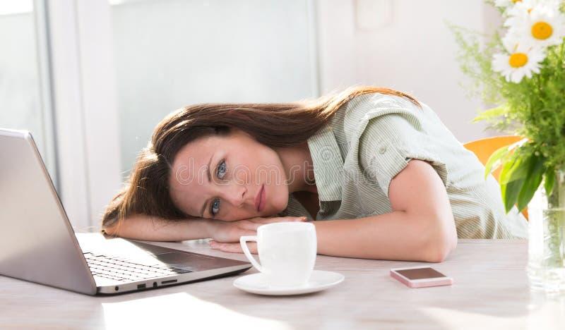 Kobieta kłama nad laptopem przy biurkiem obraz royalty free