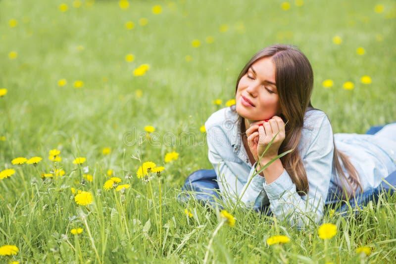 Kobieta k?a?? na trawie w parku zdjęcia royalty free