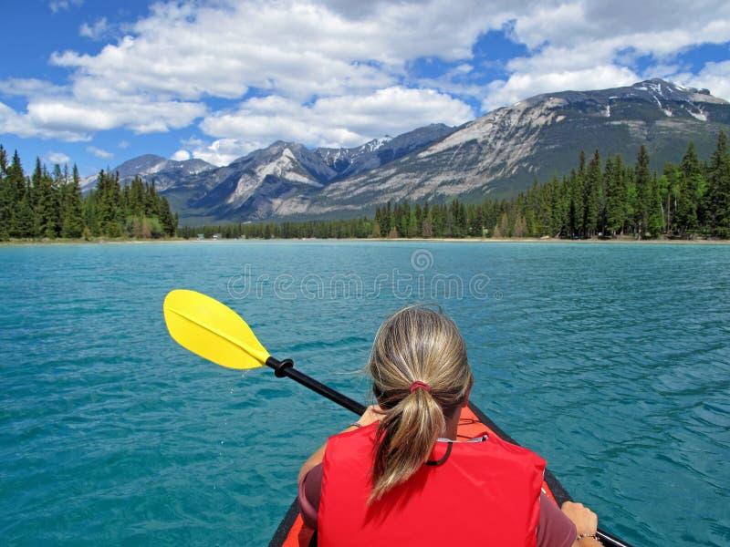Kobieta kayaking z czerwonym nadmuchiwanym kajakiem na Edith jeziorze, jaspis, Skaliste góry, Kanada fotografia royalty free