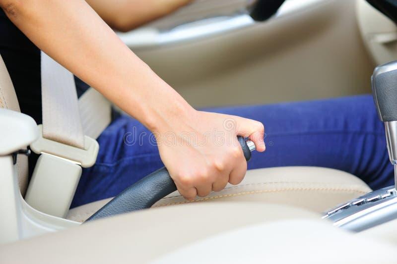 Kobieta kierowca ciągnie samochodowego ręka hamulec fotografia stock