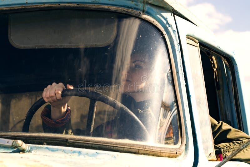 Kobieta kierowca ciężarówki w samochodzie Dziewczyna ono uśmiecha się przy kamerą i trzyma kierownicę fotografia royalty free