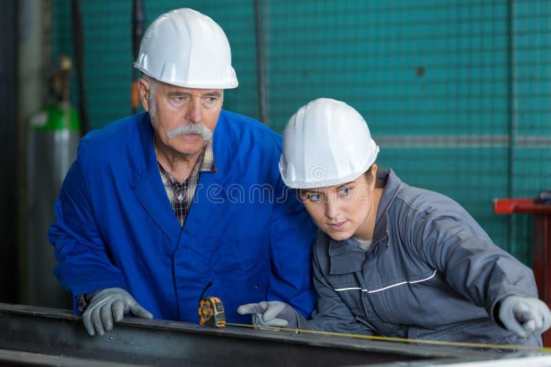 Kobieta konstruuje używać taśmy miarę z starszym nadzorcą zdjęcie royalty free