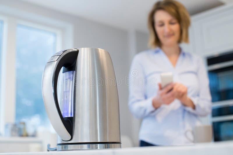 Kobieta Kontroluje Mądrze czajnika Używać App Na telefonie komórkowym obrazy royalty free