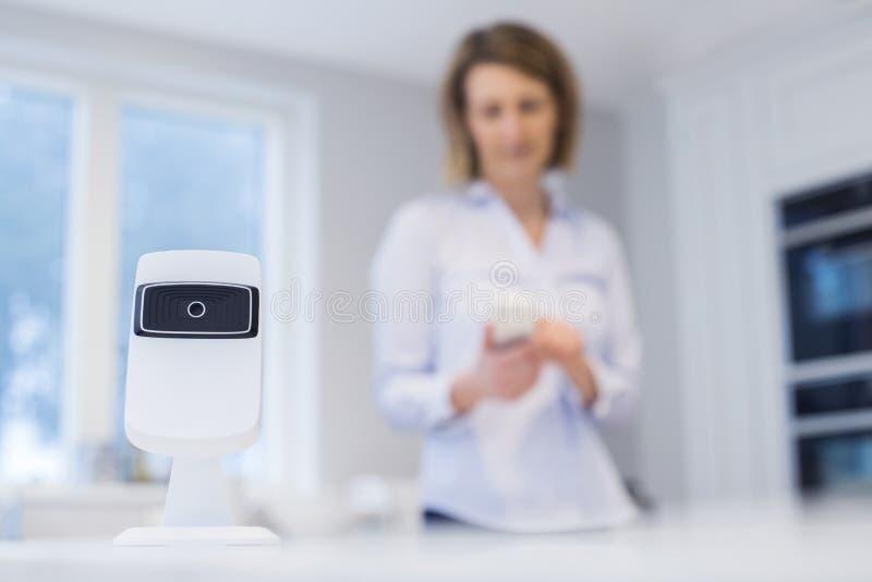 Kobieta Kontroluje Mądrze kamerę bezpieczeństwa Używać App Na Mobilnym Phon obraz stock