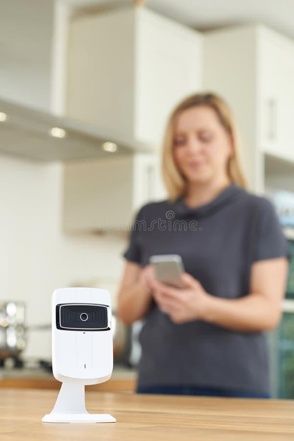 Kobieta Kontroluje Mądrze kamerę bezpieczeństwa Używać App Na Mobilnym Phon obrazy royalty free