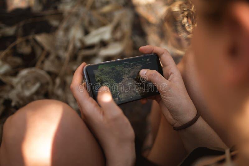 Kobieta kontroluje trutnia używać telefon komórkowego obraz royalty free