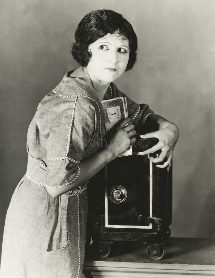 Kobieta kraść pieniądze od skrytki fotografia stock