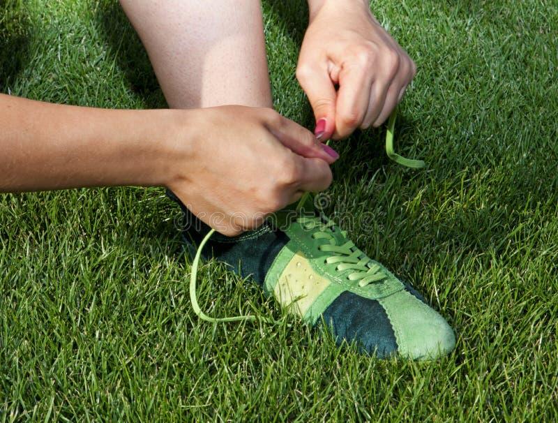 Kobieta krawatów koronki na sportów butach fotografia royalty free