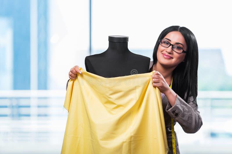 Kobieta krawczyna pracuje na nowej odzieży obraz stock