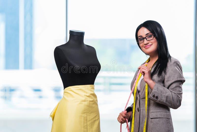 Kobieta krawczyna pracuje na nowej odzieży obraz royalty free
