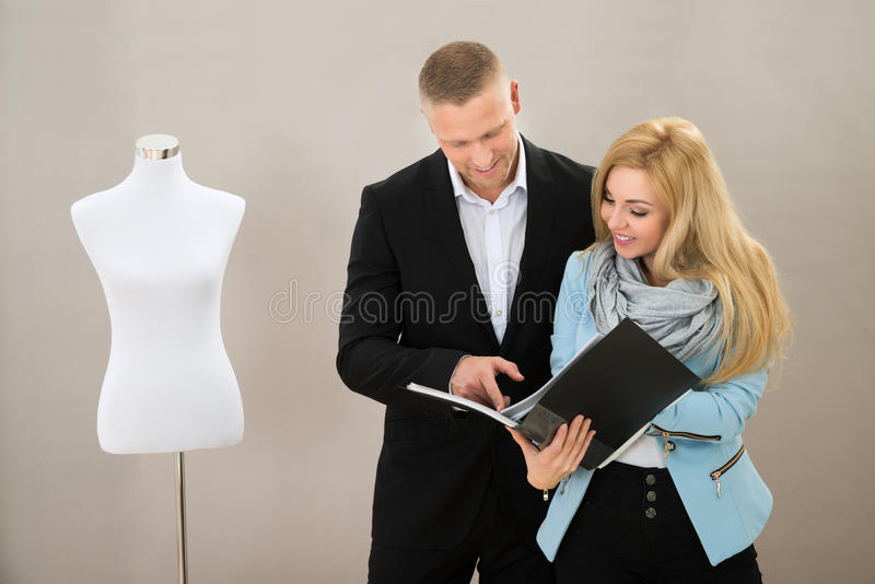 Kobieta krawczyna Z klientem Patrzeje katalog obrazy stock