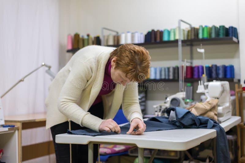 Kobieta krawczyny pracy w szwalnym studiu obraz stock