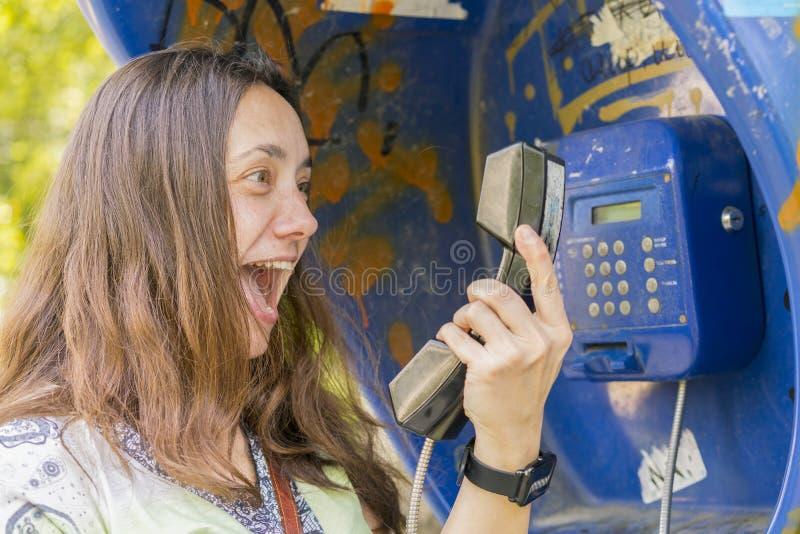 Kobieta krzyczy w handset Pojęcie bełt niekompetencja i skandal obrazy royalty free