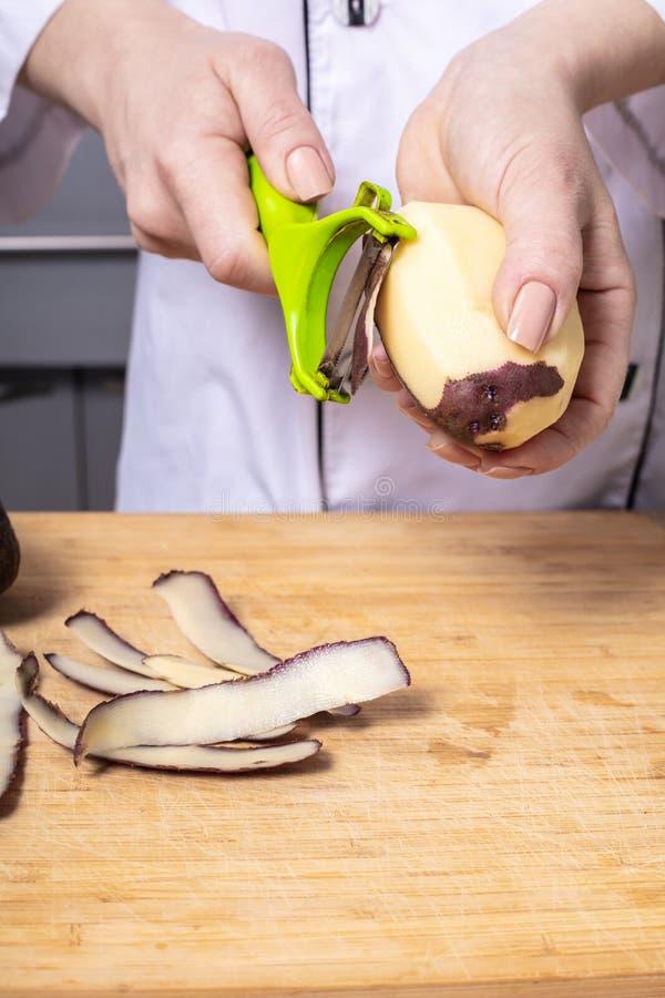 kobieta kucharz czyści grule obrazy stock