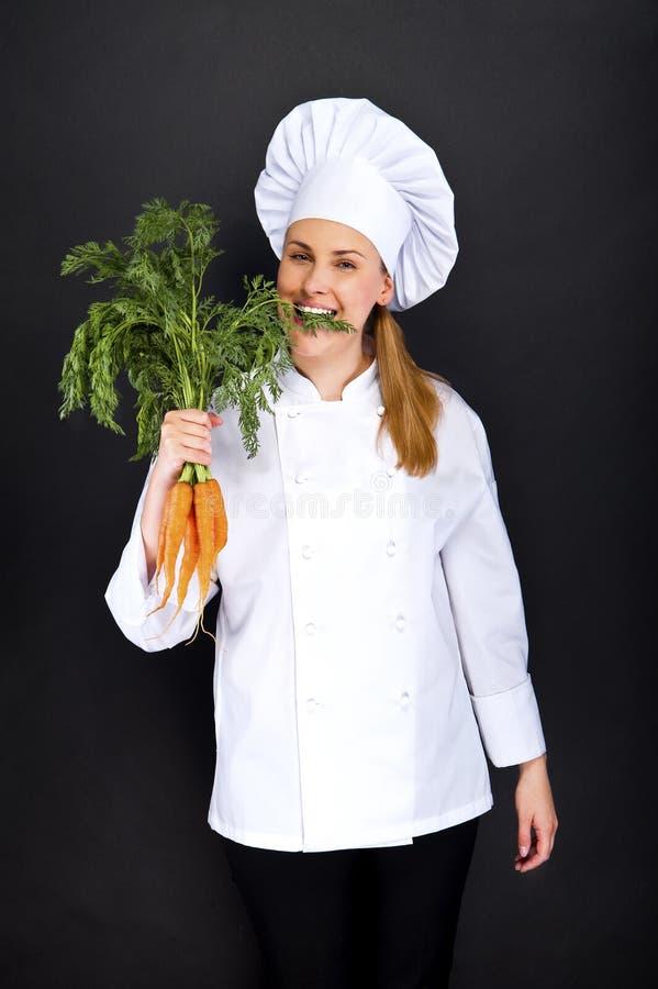 Kobieta kucharz w bielu mundurze z wiązką marchewki obraz stock