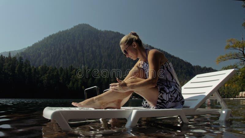 Kobieta leży na łóżku słonecznym w okularach słonecznych i w jedwabnym szale Dziewczyna spoczywa na podwodnym molo z drewna zalew zdjęcie royalty free
