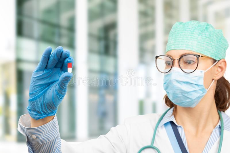 Kobieta-lekarz trzymająca tabletkę w ręku Lekarz przedstawia lekarstwo i leczenie zdjęcia stock