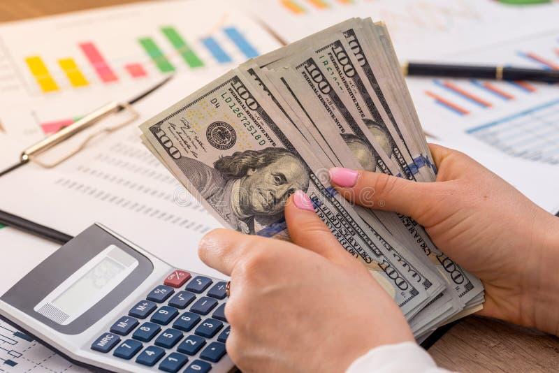 Kobieta liczy pieniądze w biurze biznesowych grafika kalkulator zdjęcie royalty free