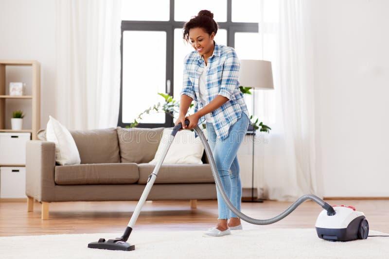Kobieta lub gospodyni domowa z pr??niowym cleaner w domu obrazy stock
