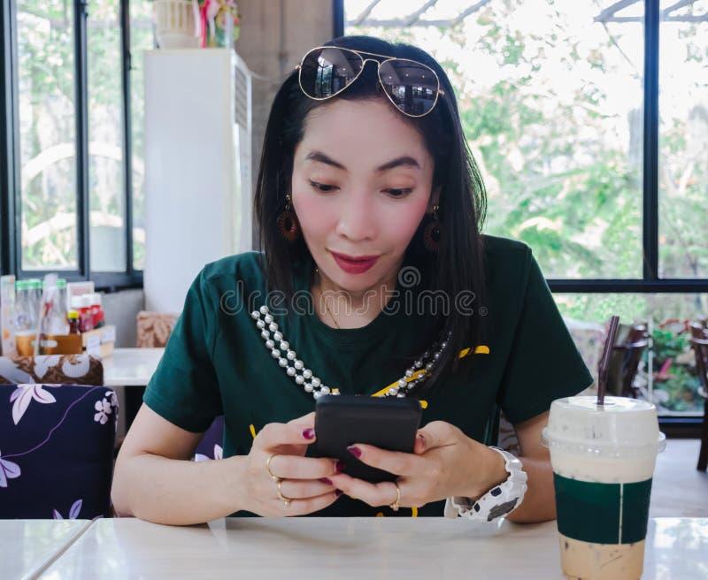 Kobieta mądrze telefon szokujący w sklep z kawą obraz royalty free