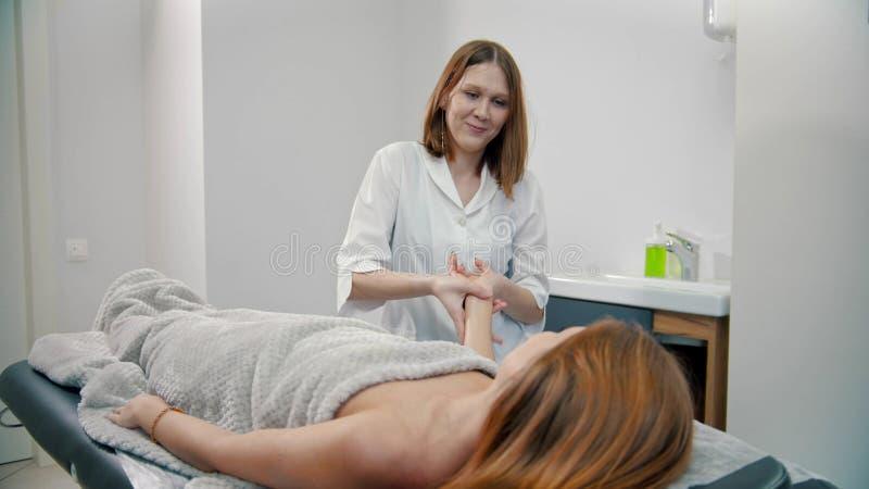 Kobieta-młoda masażystka masuje nadgarstek kobiety-klientki zdjęcia royalty free