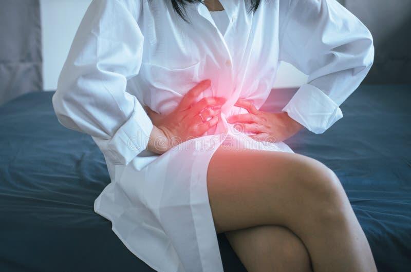 Kobieta ma bolesnego stomachache w domu, ?e?ski cierpienie od brzusznego b?lu, okres?w dr?twienia, r?ki gniesie brzucha fotografia royalty free