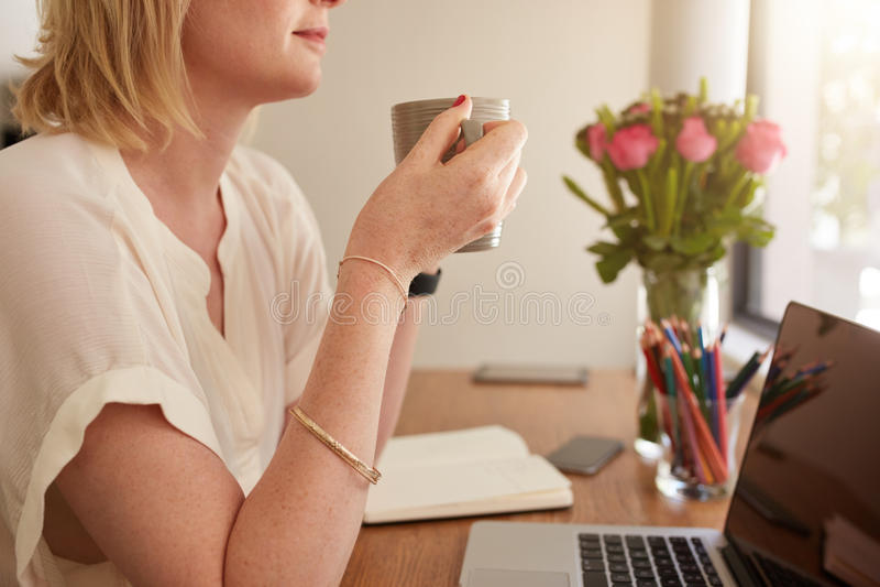 Kobieta ma kawę przy jej pracy biurkiem zdjęcia stock
