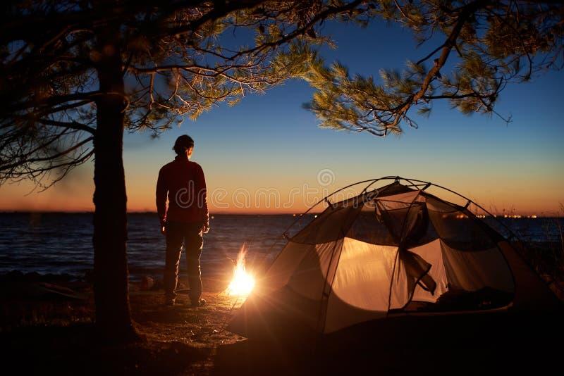 Kobieta ma odpoczynek przy nocą obozuje blisko turystycznego namiotu, ognisko na dennym brzeg pod gwiaździstym niebem obrazy royalty free
