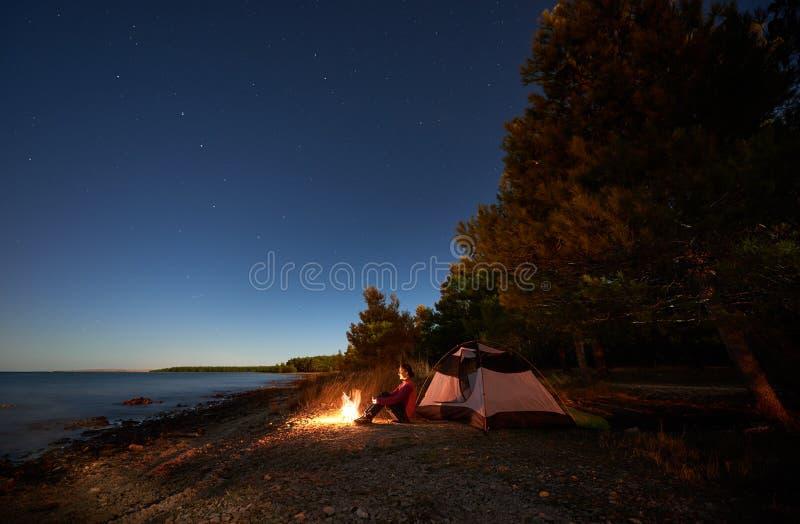 Kobieta ma odpoczynek przy noc? obozuje blisko turystycznego namiotu, ognisko na dennym brzeg pod gwia?dzistym niebem fotografia stock