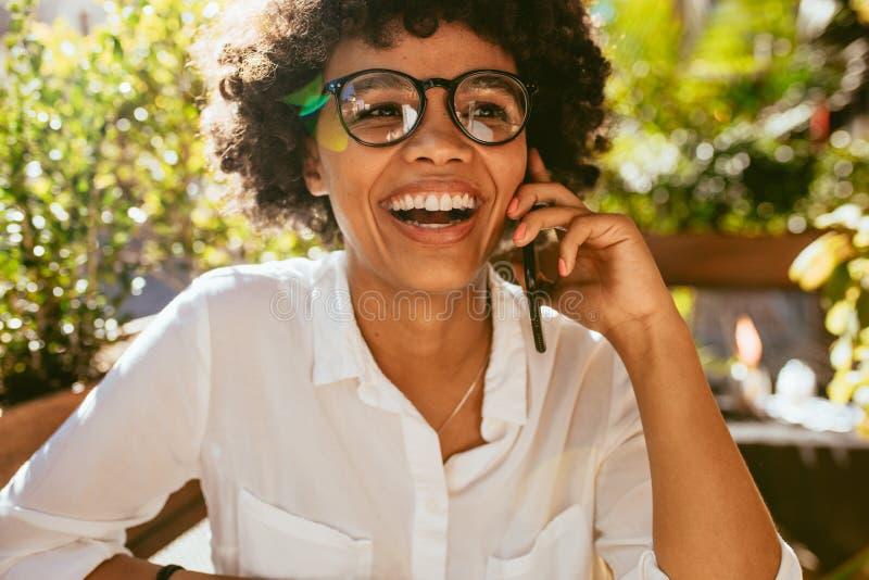 Kobieta ma rozmowę na telefonie przy kawiarnią zdjęcia stock