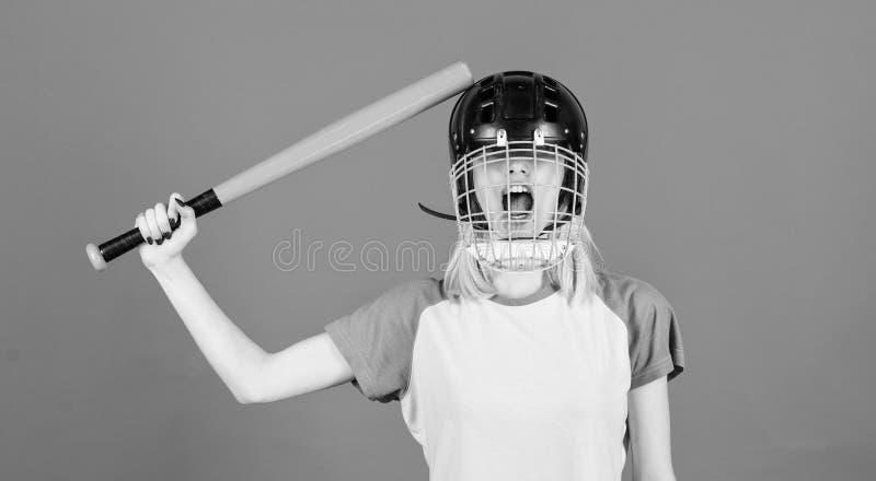Kobieta ma zabawę podczas baseball gry Dziewczyny blondynki odzieży baseballa ładny hełm i chwyt uderzamy na błękitnym tle Bije o zdjęcie royalty free