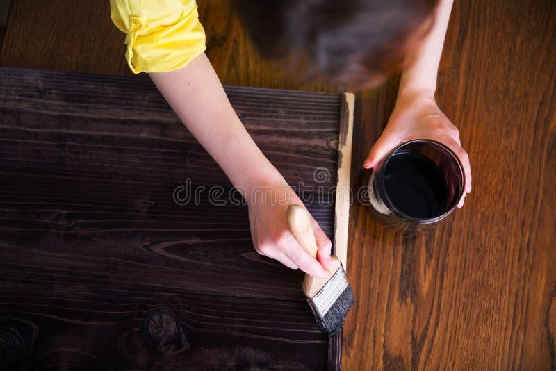 Kobieta maluje deski z plamą heban drewniana plama obraz royalty free