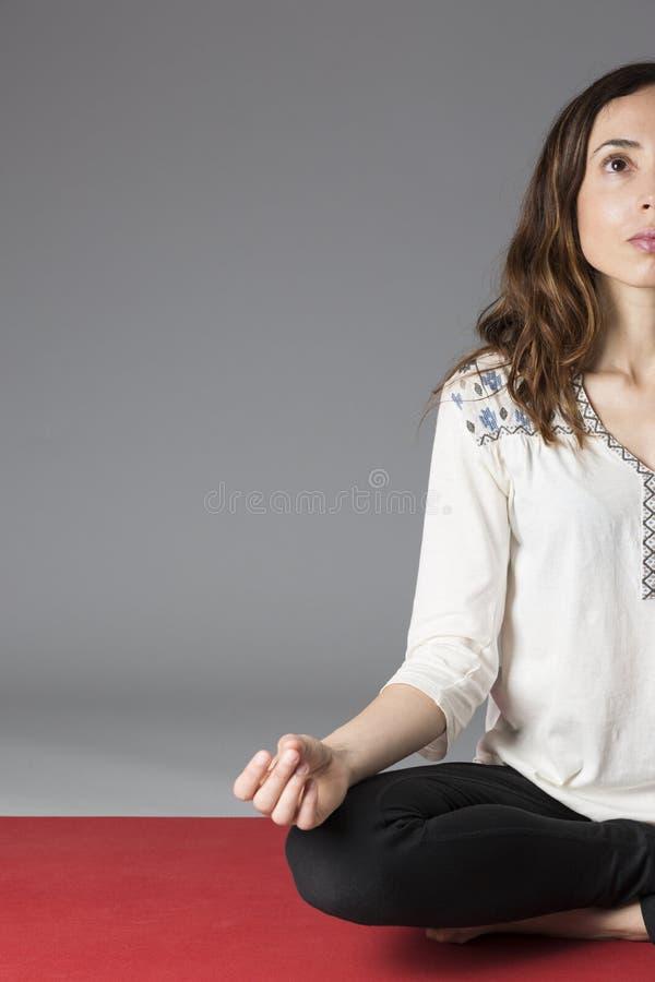 Kobieta medytuje na jej joga macie obrazy royalty free